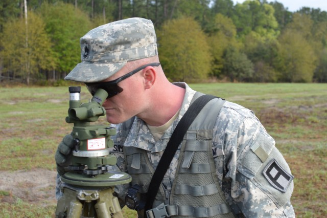 Sgt. 1st Class Alan Simmons, 2nd Battalion, 306th Field Artillery Regiment observer-coach/trainer, looks through an aiming circle to provide a point of reference for the Howitzer cannons.