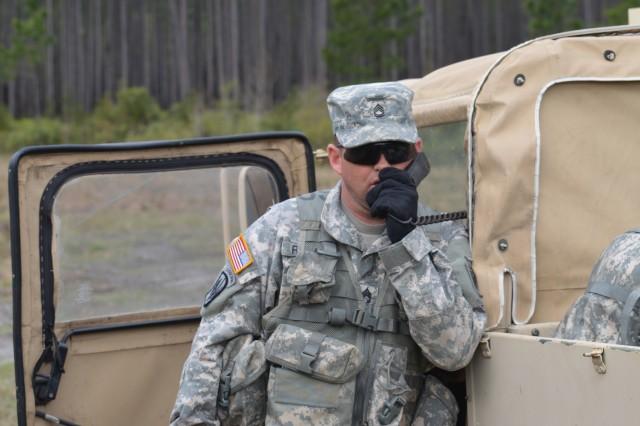 Sgt. 1st Class Justin Reeves, 2-306th Field Artillery Regiment observer-coach/trainer, listens in during a radio transmission between the fire direction center and the radio transmission officer. He will use the information to provide feedback on how effective radio communications are during crew drills.
