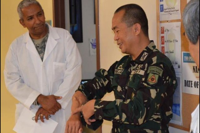 Col. Cirilito Sobejana (right), the Armed Forces of the Philippines (AFP) Philippine Army G3, visited Tripler Army Medical Center (TAMC) April 7, 2015, and visits with Staff Vascular Surgeon Maj. Farhan Ayubi (left), DO, TAMC Vascular Surgery Department. Sobejana expressed gratitude for treatment he received 20 years ago at TAMC that saved his career in the Armed Forces of the Philippines and the use of his right arm. Sobejana is a recipient of the AFP's equivalent to the U.S. Medal of Honor for actions taken against a terrorist organization in 1995. (U.S. Army photo by James Guzior, Tripler Army Medical Center Public Affairs)