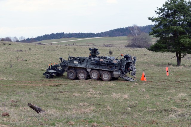 A Soldier with 1st Platoon, Regimental Engineering Squadron, 2nd Cavalry Regiment, runs into an M1132 Stryker engineer squad vehicle April 13, 2015, during Saber Junction 15 at Joint Training Military Area in Hohenfels, Germany. The regiment is conducting scenario training exercises this week in preparation for a force-on-force decisive action training exercise, or DATE, that begins next week and incorporates 4,700 military members from 17 countries.