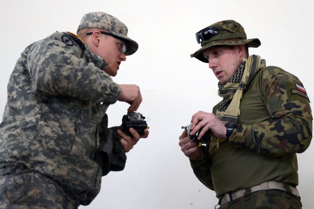 Sgt. Michael Kwiatkowski (left), attached to the 1st Squadron, 2nd Cavalry Regiment, explains how to set up MILES (multiple integrated laser engagement system) for weapons before a situational training exercise April 13, 2015, during Saber Junction 15 at Joint Training Military Area in Hohenfels, Germany. Kwiatkowski's language skills are being used to help Polish Army 1st Lt. Micheal Kulas, acting executive officer for the Polish army's 3rd Company, 12th Mechanized Brigade, prepare for the mission. The regiment is conducting situational training exercises this week in preparation for a force-on-force decisive action training exercise, or DATE, that begins next week and incorporates 4,700 military members from 17 countries.