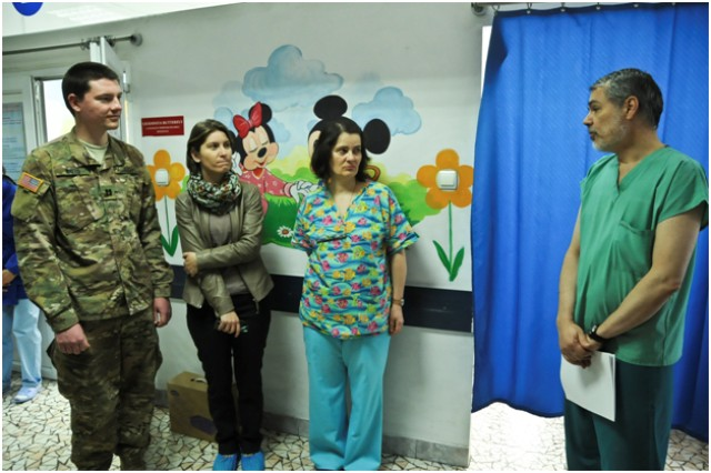Capt. Nathaniel Watts (left,) a field surgeon assigned to Headquarters and Headquarters Troop, 2nd Squadron, 2nd Cavalry Regiment along with Valentina Maghirescu (center left,) the director of Fundatia Inocenti, a humanitarian foundation that serves children and families, and Dr. Tatiana Ciomartan (center,) a local doctor, speak with Dr. Craiu Mihaj, an emergency room doctor, about medical care during the unit's visit with medical staff at the Institute of Mother and Childcare in Bucharest, Romania, Apr. 10, 2015.