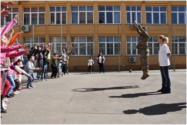 Sgt. Christopher Tupper, a combat medic assigned to Headquarters and Headquarters Troop, 2nd Squadron, 2nd Cavalry Regiment, shows students how to do the high jumper portion of the Army's Physical Readiness Training during his unit's visit at a local school in Bucharest, Romania, Apr. 10, 2015.