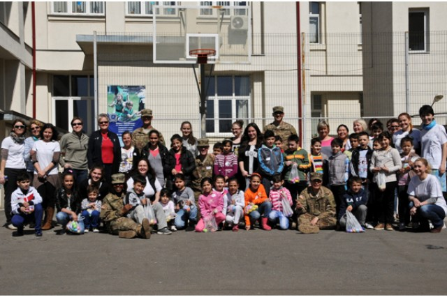 Combat Medics assigned to Headquarters and Headquarters Troop, 2nd Squadron, 2nd Cavalry Regiment, pose for a photo with students during their visit to a local school in Bucharest, Romania, Apr. 10, 2015.