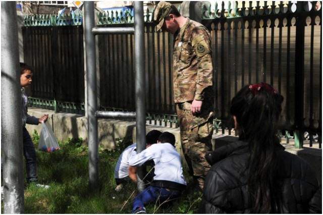 Capt. Nathaniel Watts, a field surgeon assigned to Headquarters and Headquarters Troop, 2nd Squadron, 2nd Cavalry Regiment, helps students find hidden eggs during an Easter egg hunt while visiting a local school in Bucharest, Romania, Apr. 10, 2015.
