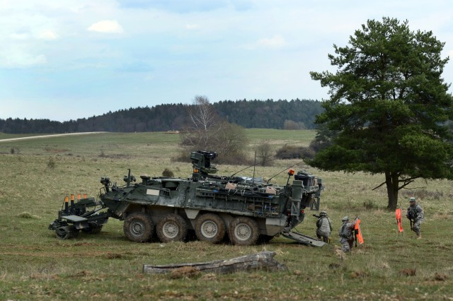 Soldiers, with 1st Platoon, Alpha Troop, Regimental Engineering Squadron, 2nd Cavalry Regiment, place flags to mark a lane cleared for maneuver forces at Joint Multinational Training Area in Hohenfels, Germany, April 13, 2015.