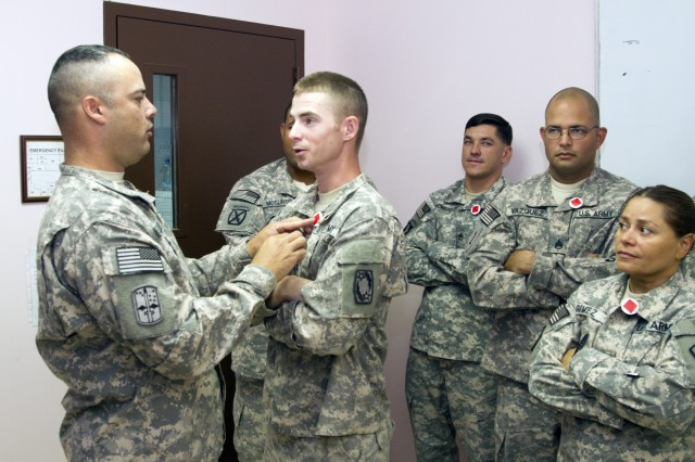 Sgt. 1st Class Frank Desario, 1st Brigade Combat Team, 1st Infantry Division equal opportunity advisor, pins a badge indicating social status on Staff Sgt. Michael Holstrom during the Equal Opportunity Leaders' Course at Camp Arifjan, Kuwait, July 24, 2015. The students are participating in an exercise that demonstrates power in units and how it it can affect a Soldier's actions.