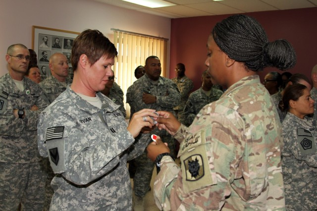 Capt. Jennifer Ryan and Staff Sgt. Franteshia Miller, students of the Equal Opportunity Leaders' Course at Camp Arifjan, Kuwait, July 24, 2015, switch social status badges during a training exercise.