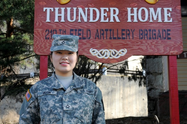 CAMP CASEY, South Korea -- Pfc. Hyeyoung Moon, a behavioral health specialist from Houston, Texas assigned to Headquarters and Headquarters Battery, 210th Field Artillery Brigade, 2nd Infantry Division, pose for the camera in front of sign of Thunder Home, March 23, 2015 at Camp Casey, South Korea. Moon currently works as an Embedded Behavioral Health Team member at Thunder Home which serves as a haven for the brigade Soldiers to relax and receive extra support when dealing with personal problems or concerns.