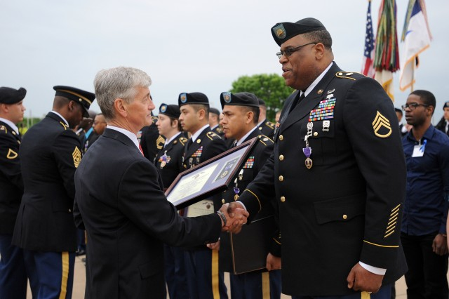Army Secretary John M. McHugh presents a Purple Heart to Staff Sgt. Alonzo Lunsford Jr. during the Fort Hood Purple Heart and Defense of Freedom Medal Ceremony at III Corps Headquarters, Fort Hood, Texas, April 10, 2015.