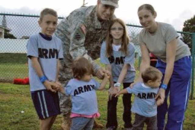 Staff Sgt. Derrick (top) and Sgt. Alyssa Ott enjoy a morning out with their children Amarra (2nd from left), Alayna, Dominic (left) and Daxton (far right) at PT in the Park, an event hosted by Youth Sports. for the Month of the Military Child at Schofield School Age Center, April 7.