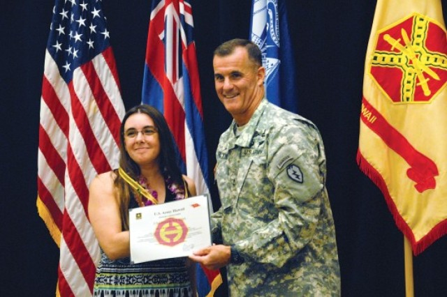 Amanda Crowell, Army Family Team Building volunteer program manager, receives the Na Koa Award, which features the Lazy H insignia, from Maj. Gen. Charles Flynn, April 14, at the Volunteer Recognition Ceremony at Schofield Barracks.