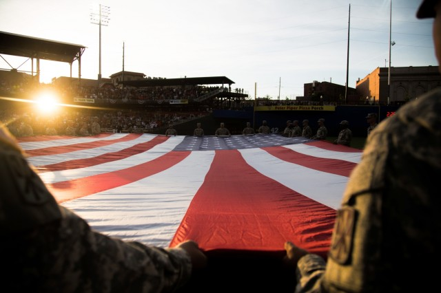 Soldiers 11th Air Defense Artillery Brigade, unfurl a field size flag during the El Paso Chihuahuas opening night, at El Paso, Texas, April 9, 2015. More than 50 Soldiers from across Fort Bliss, Texas supported the opening day for the El Paso Chihuahuas, a AAA baseball affiliate for the Sand Diego Padres. (U.S. Army photo by: Sgt. Marcus Fichtl, 24th Press Camp)