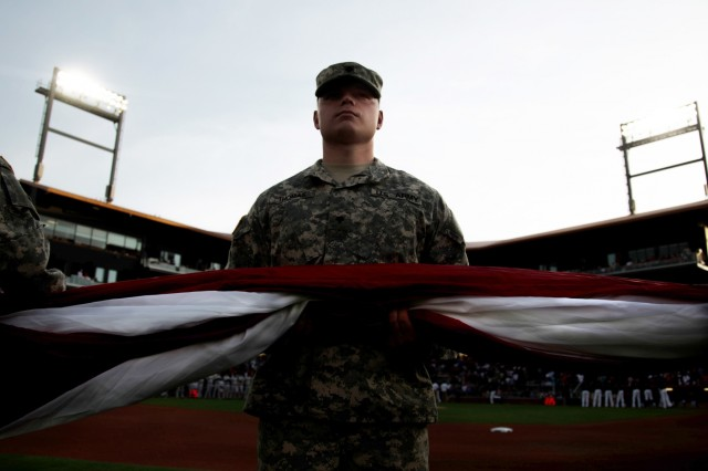 A Soldier 11th Air Defense Artillery Brigade, prepares to unfurl a field size flag during the El Paso Chihuahuas opening night, at El Paso, Texas, April 9, 2015. More than fifty Soldiers from across Fort Bliss, Texas supported the opening day for the El Paso Chihuahuas, a AAA baseball affiliate for the Sand Diego Padres. (U.S. Army photo by: Sgt. Marcus Fichtl, 24th Press Camp)