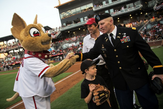 Chico, the El Paso Chihuahuas mascot shakes hands with Col. Michael J. Hester, Fort Bliss garrison commander as congressman Beto O'Rourke looks on during the El Paso Chihuahuas opening night, at El Paso, Texas, April 9, 2015. More than fifty Soldiers from across Fort Bliss, Texas supported the opening day for the El Paso Chihuahuas, a AAA baseball affiliate for the Sand Diego Padres. (U.S. Army photo by: Sgt. Marcus Fichtl, 24th Press Camp)