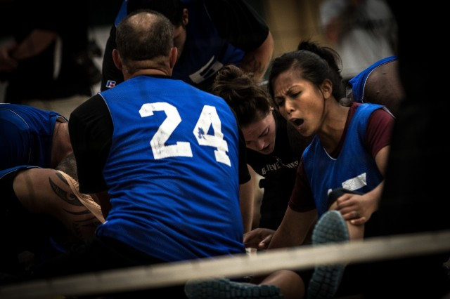 Sgt. Madeleine Morales, Waipahu, Hawaii, native, Army Trials athlete, Warrior Transition Unit, huddles with her team during a game of seated volleyball as part of the Army Trials, Fort Bliss Texas, April 1, 2015. The Army Trials showcase the resilient spirit of wounded, ill and injured Soldiers and veterans. Participants in Army Trials include athletes with spinal cord injuries, traumatic brain injuries, visual impairments, serious illnesses and amputations. The results of the games help determine which Army athletes compete on the Department of Defense level Army competition team. Morales fights PTSD she sustained from a deployment to Iraq. (U.S. Army photo by Sgt. Marcus Fichtl, 24th Press Camp)