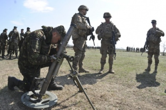A Romanian soldier (left,) assigned to the Romanian Land Forces, tries out an M224 60mm lightweight mortar system as Troopers (center, right,) assigned to 2nd Squadron, 2nd Cavalry Regiment, supervise during a static display by the unit after participating in the opening ceremony for Wind Spring 2015 at Smardan Training Area, Romania, April 16, 2015. The Wind Spring 2015 exercise is aimed at maintaining and increasing interoperability between NATO Allies.