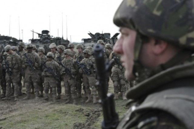 A Romanian soldier (right), assigned to the Romanian Land Forces (ROULF), watches as Troopers assigned to 2nd Squadron, 2nd Cavalry Regiment, along with Romanian soldiers assigned to ROULF and British soldiers assigned to the Coldstream Guards, participate in the opening ceremony for Wind Spring 2015 at Smardan Training Area, Romania, April 16, 2015. The Wind Spring 2015 exercise is aimed at maintaining and increasing interoperability between NATO Allies.