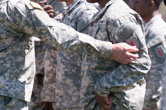 Soldiers of 1st Infantry Division Sustainment Brigade change their unit patches to the 'Big Red One' patch April 22, 2015 at Cavalry Parade Field on Fort Riley, Kansas. The changing of the patches was part of an inactivation/activation ceremony and the 1st Infantry Division Sustainment Brigade also uncased new colors for the ceremony. (Staff Sgt. Jerry Griffis, 1st inf. Div.)