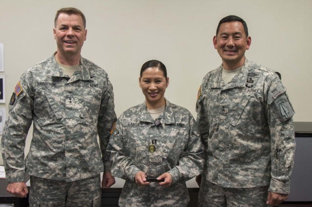 (From left to right) Maj. Gen. Theodore Harrison, commanding general of Army Contracting Command, Capt. Miracle Garcia and Maj. Gen. K.K. Chinn, deputy commanding general of U.S. Army Special Operations Command after presenting Garcia with an award recognizing her as the 2014 U.S. Special Operations Command Outstanding Contingency Contracting Officer of the Year for her success while serving as a Contracting Officer supporting Army Special Operations Forces.