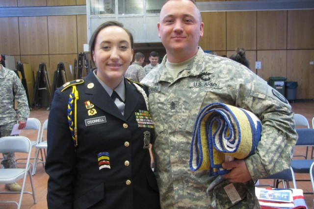 "Cadet Kerinne O'Donnell stands with her father, 1st Sgt. Willard O'Donnell of the 12th Combat Aviation Brigade, during the March 26 ""Quilts of Valor"" ceremony at Ansbach Middle/High School. Cadets presented handcrafted quilts to 14 other Soldiers of 12th CAB during the ceremony. (U.S. Army photo by Cadet Kaitlyn Pyrtle, 9th Junior ROTC Battalion)"