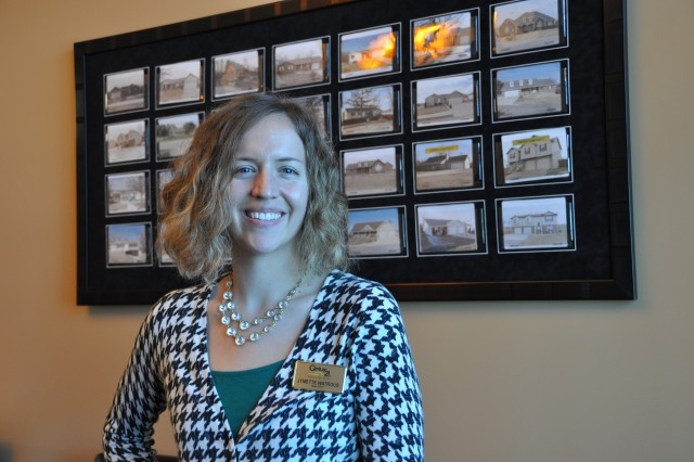 Jymette Watrous stands by a board of home listings during her Soldier for Life internship, which she chose to complete at a local realtor.