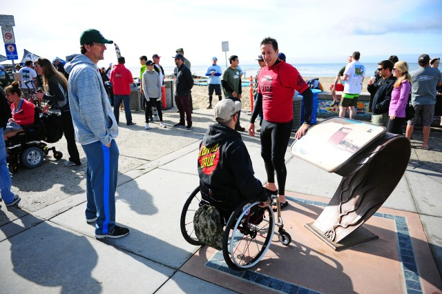 "PRESIDIO OF MONTEREY, Calif. -- Professional Santa Cruz surfer Ken ""Skindog"" Collins talks with an Operation Surf participant during the morning prior to a day of surfing for wounded service members and veterans in Capitola April 25."