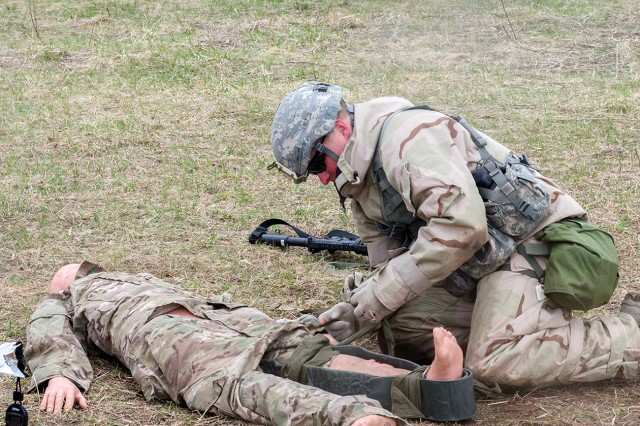 A Soldier with 2nd Battalion, 87th Infantry Regiment, 2nd Brigade Combat Team, 10th Mountain Division (LI), places a splint on a mannequin's leg April 22, as he performs buddy-aid while working his way through an individual task lane of Expert Infantryman Badge testing. The EIB was instituted in 1944 to build esprit de corps within U.S. infantry units.