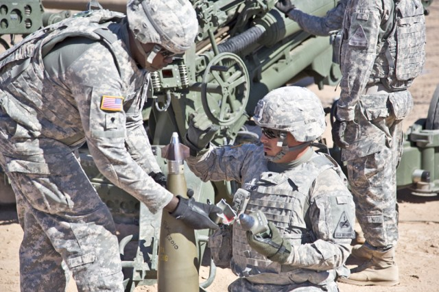 Soldiers from the 4th Battalion, 27th Field Artillery Regiment from Fort Bliss, Texas, remove the Precision Guidance Kit (PGK) canard cover and ensure the canards spin before firing the round during Early User Assessment at Yuma Proving Ground, Arizona, October 2012.