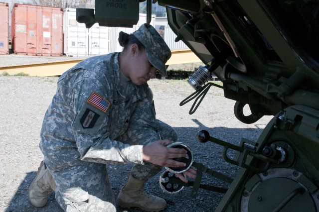 Sgt. Melissa Pinney, M1135 Stryker Nuclear, Biological, Chemical, Reconnaissance vehicle commander, 401st Chemical Company, and North Providence, R.I., native, attaches wheels for sample taking to a newly-fielded vehicle. (U.S. Army photo by Staff Sgt. Debralee Best)