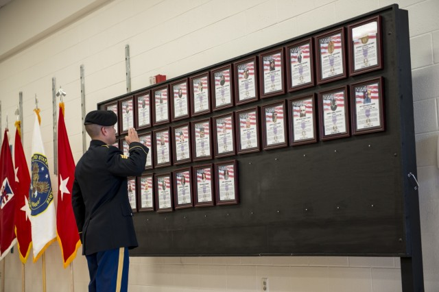 Sgt. Christian Soto, with the 416th Theater Engineer Command (TEC), salutes a fallen Soldier after placing his plaque onto a display during a Fallen Heroes Memorial Wall ceremony hosted at the 416th TEC headquarters in Darien, Ill., May 2, to honor 46 Army Reserve Soldiers who belonged to either the 416th or 412th TEC and lost their lives while serving overseas. The ceremony was a combined effort of the two TECs and the Engineer Command Association, which funded the costs associated with the ceremony and helped organize the event. (U.S. Army photo by Sgt. 1st Class Michel Sauret)