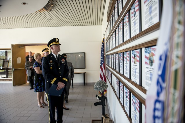 Maj. Gen. Lewis Irwin, commanding general of the 416th Theater Engineer Command (TEC), pays respect to the Fallen Heroes Memorial Wall during a ceremony hosted at their headquarters in Darien, Ill., May 2, to honor 46 Army Reserve Soldiers who belonged to either the 416th or 412th TEC and lost their lives while serving overseas. The ceremony was a combined effort of the two TECs and the Engineer Command Association, which funded the costs associated with the ceremony and helped organize the event. (U.S. Army photo by Sgt. 1st Class Michel Sauret)