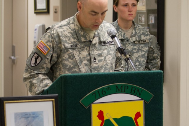 Staff Sgt. Jonathan Rose, the plans noncommissioned officer for the 510th Military Police Detachment, 716th Military Police Brigade, supported by the 101st Sustainment Brigade, 101st Airborne Division (Air Assault), serves as narrator during a memorial service the MPs held for military working dog Samu April 22, 2015, at Fort Campbell, Kentucky. Standing behind Rose is Spc. Melaney Brown, Samu's most recent dog handler, also with the 510th MP Det., who, shortly before his untimely death, spent eight months training with Samu and validated with her battle buddy, which certified them to carry out patrol and explosive detection missions both downrange and in garrison.