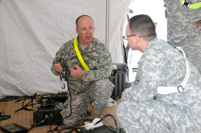 Staff Sgt. Michael O'Rourke, a signal systems support specialist with the 3rd ESC, explains the process of setting up a SINCGARS radio system to Pfc. Timothy Cruz, an information technology specialist with the 3rd ESC, during the 3rd ESC's Early Entry Command Post set up April 20 at the Mission Command Training Center on Fort Knox. The EECP is a Sustainment Mission Command Headquarters and is capable of providing a variety of logistical functions.
