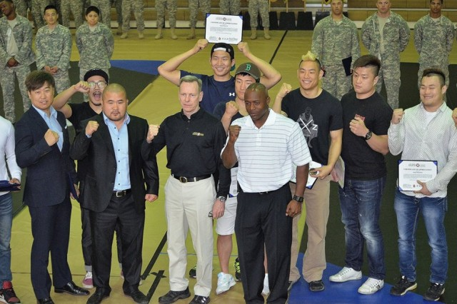 Eighth Army Commanding General Lt. Gen. Bernard Champoux and Eighth Army Command Sgt. Maj. Edward Mitchell pose with mixed martial artists from the Ultimate Fighting Championship and the Top Fighting Championship May 2 at U.S. Army Garrison Yongsan in Seoul, Republic of Korea. The professional fighters put on a demonstration during the Eighth Army Modern Army Combatives Tournament in the spirit of the partnership between the U.S. and South Korea. (Photos and story by Tim Oberle, Eighth Army Public Affairs)