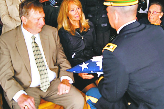Capt. Ryan Ball, U.S. Army Military Police School, presents an American flag to the widow and brother of a Vietnam-era Soldier whose remains were recently repatriated to the United States from Vietnam 45 years after he was missing in action. Ball and the Soldier share the same hometown.