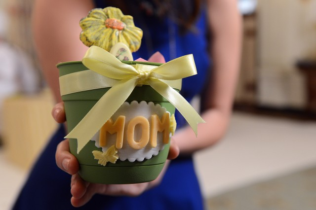 A White House staff member displays a gift made by a child during a Mother's Day tea hosted by First Lady Michelle Obama and Dr. Jill Biden to honor military mothers, May 8, 2015.