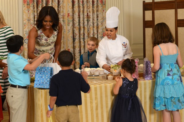 First Lady Michelle Obama helps military children create Mother's Day gifts during a Mother's Day tea honoring military mothers at the White House, May 8, 2015