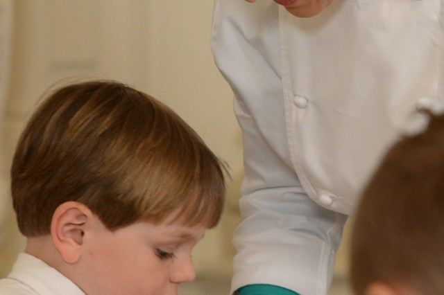 White House chef Susan Morrison helps a military child with a gift for his mother, during a Mother's Day tea at the White House, May 8, 2015