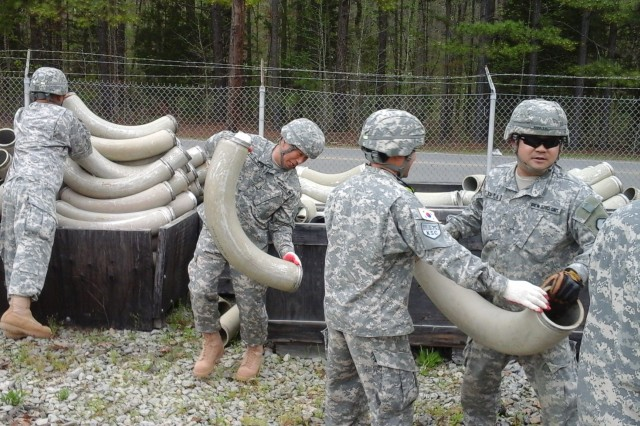 Members of the Korean Service Corps participate in the Fiscal Year 2015 U.S. Forces Command Petroleum Training Module field exercise at Fort Pickett, Va. The 35-member KSC team practiced its ability to rapidly establish a series of pipes to simulate a petroleum distribution system during a contingency situation. (Photo courtesy of the Korea Service Corps)