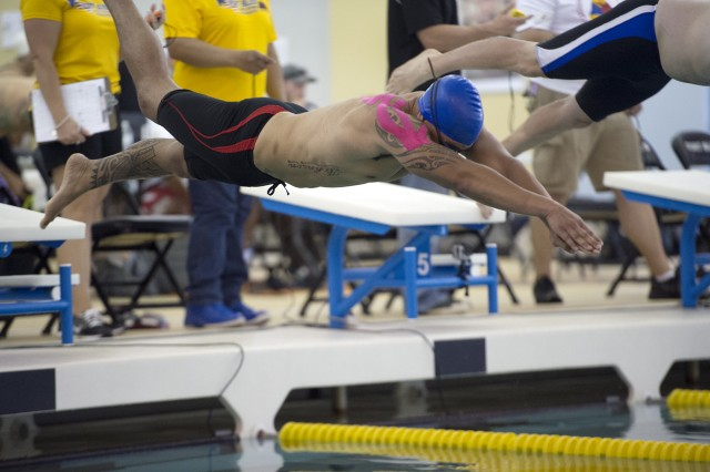 Sgt. Blake Johnson dives into a pool during the Army Trials on Fort Bliss, Texas, during the end of March. He earned bronze medals in 50-meter freestyle, 50-meter backstroke and 100-meter freestyle and earned the right to compete in the Department of Defense Warrior Games, set for June 19-28, 2015.