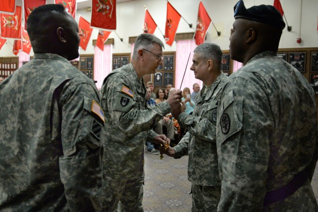 Col. Peter Nielsen, center left, General Leonard Wood Army Community Hospital commander, passes the NCO sword to incoming Command Sgt. Maj. David Williams, during the hospital's change-of-responsibility ceremony Friday. Looking on are Command Sgt. Maj. Tony Williams, left, outgoing CSM, and Staff Sgt. Michael Armstead.
