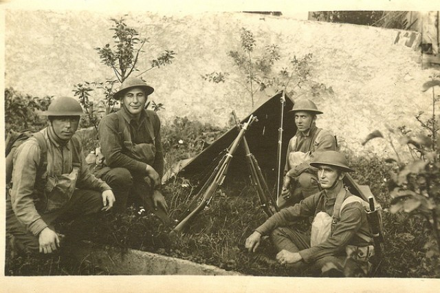 Soldiers resting in grass by pup tent (Sgt. William Shemin shown kneeling second from the left).