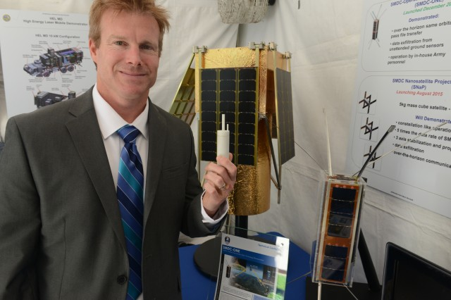 Dr. Travis Taylor, senior scientist for Space Division, U.S. Army Space and Missile Defense Command - Tech Center, at Redstone Arsenal, Ala., discusses Army space satellites during Lab Day at the Pentagon, May 14, 2015. He is shown holding a plastic and liquid nitric oxide container, which propels the satellite into low-Earth orbit after it leaves the mothership. Behind him is the imagery satellite and to the right is the smaller data and voice satellite.