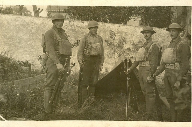 Photo of Sgt. William Shemin (far left) and three Soldiers in front of pup tent.