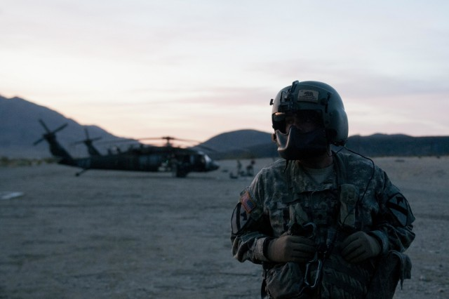 A Soldier with Company A, 3rd Assault Helicopter Battalion, 227th Aviation Regiment, 1st Air Cavalry Brigade, 1st Cavalry Division waits for the other crewmembers to finish prepping their UH-60 Black Hawks for flight May 11 at Fort Irwin, California. The battalion left the National Training Center early in the morning to reach Fort Bliss, Texas, before dark to rest and continue their trip back to Fort Hood, Texas. (U.S. Army photo by Sgt. Brandon Banzhaf, 3rd Armored Brigade Combat Team, 1st Cavalry Division.)