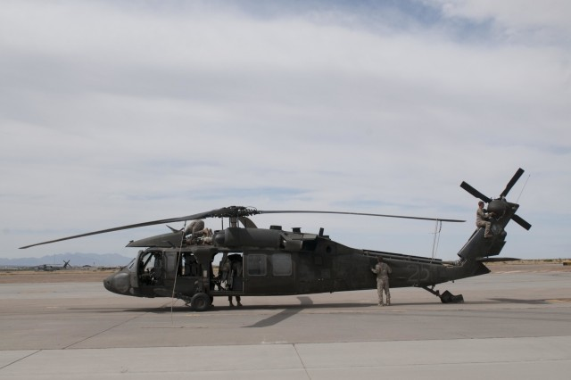 Four crew members with the 3rd Assault Helicopter Battalion, 227th Aviation Regiment, 1st Air Cavalry Brigade, 1st Cavalry Division perform their checks on the UH-60 Black Hawk helicopter after a day-long trip from Fort Irwin, California, to Fort Bliss, Texas, May 11. The battalion made several stops for refueling along the way, with the crews checking their aircraft before flying and after landing at each stop. (U.S. Army photo by Sgt. Brandon Banzhaf, 3rd Armored Brigade Combat Team, 1st Cavalry Division.)