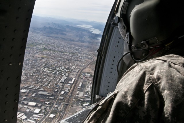 A Soldier with Company A, 3rd Assault Helicopter Battalion, 227th Aviation Regiment, 1st Air Cavalry Brigade, 1st Cavalry Division looks out the window of a UH-60 Black Hawk helicopter above a city in Arizona. The trip from California to Texas took them two days and more than 1,100 miles. (U.S. Army photo by Sgt. Brandon Banzhaf, 3rd Armored Brigade Combat Team, 1st Cavalry Division)