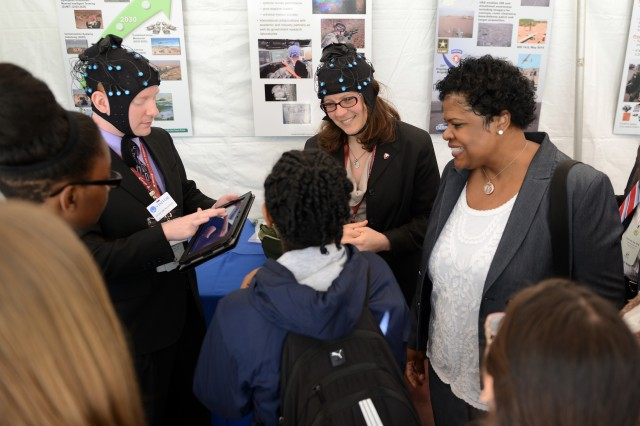 "Jean Vettel, Ph.D., right, a neuroscientist with the Army Research Laboratory at Aberdeen Proving Ground, Md., wears headgear lined with brain wave-sensing EEG, or ""electroencephalography"" sensors, in the Pentagon courtyard as part of the display she manned at DOD Lab Day, May 14, 2015. She and fellow researcher, Jonroy Canady, left, speak with area high school students, who attended the lab day event."