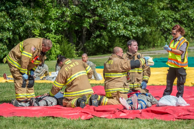 Firemen render first aid to simulated tornado victims.